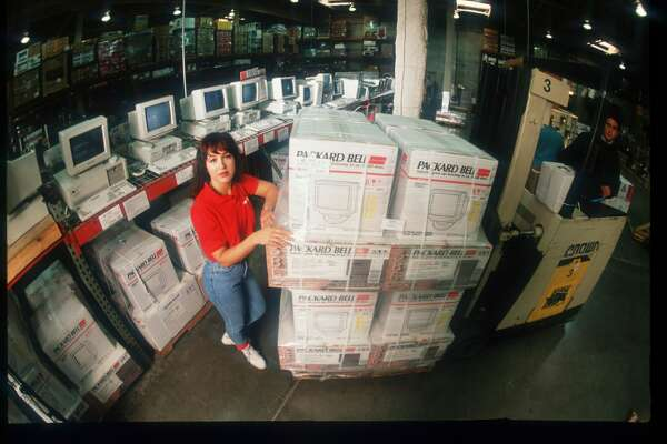 An unidentified woman stands near a stack of Packard Bell computers at Costco Warehouse on December 11, 1991 in California.