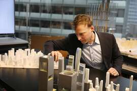 Mark Schwettmann, director Skidmore, Owings & Merrill, arranges a group of study models next to first generation study models from the same project, at Skidmore, Owings & Merrill,  on Wednesday, March 6,  2019 in San Francisco, Calif.