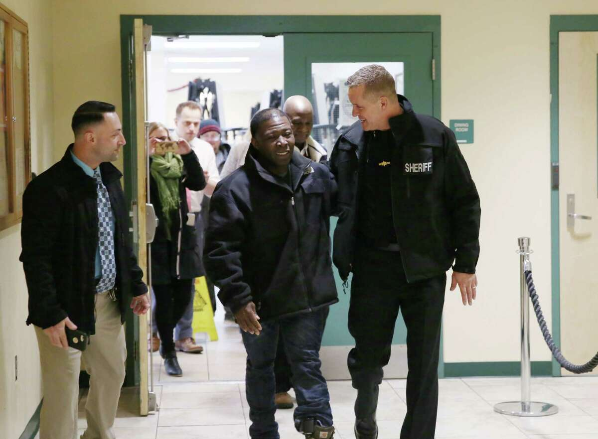 Kinimo Ngoran, chef at the Capital City Rescue Mission, smiles as he walks into the building with Albany County Sheriff Craig Apple after being released from ICE detention in Buffalo on Wednesday, March 6, 2019 at the Capital City Rescue Mission in Albany, NY. (Phoebe Sheehan/Times Union)