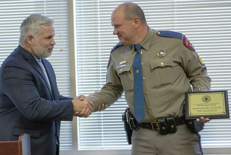 Montgomery County district attorney Brett Ligon, left, shakes hands with DPS Sgt. Dean Barnhill after Barnhill accepted the 2018 DWI Agency of the Year award Wednesday, March 6, 2019 at the Lee G. Alworth Building in Conroe. Photo: Cody Bahn, Houston Chronicle / Staff Photographer / © 2018 Houston Chronicle