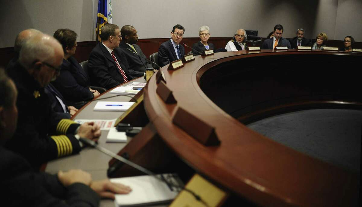 Then-Gov. Dannel P. Malloy, center, speaks during a presentation of the final report from the Sandy Hook Advisory Commission at the Legislative Office Building, March 6, 2015, in Hartford. The commission was formed to provide a review current policy and make recommendations in the areas of public safety, mental health, and gun violence prevention after the 2012 killings of 20 first-graders and six adults at Sandy Hook Elementary School.