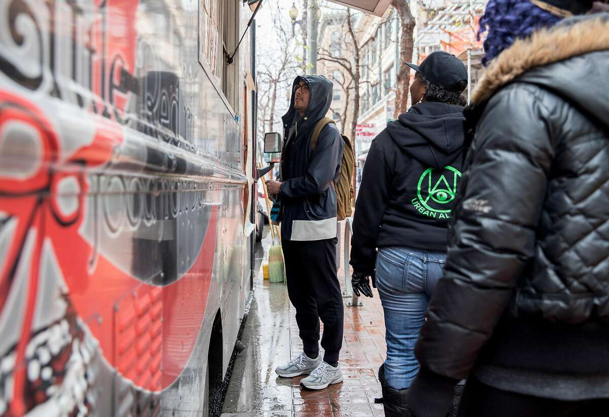 Zendesk employee Brian Green (center) orders food from Little Red Riding food truck during a food truck soft opening along Market Street near 6th Street in San Francisco, Calif. Wednesday, March 6, 2019.
