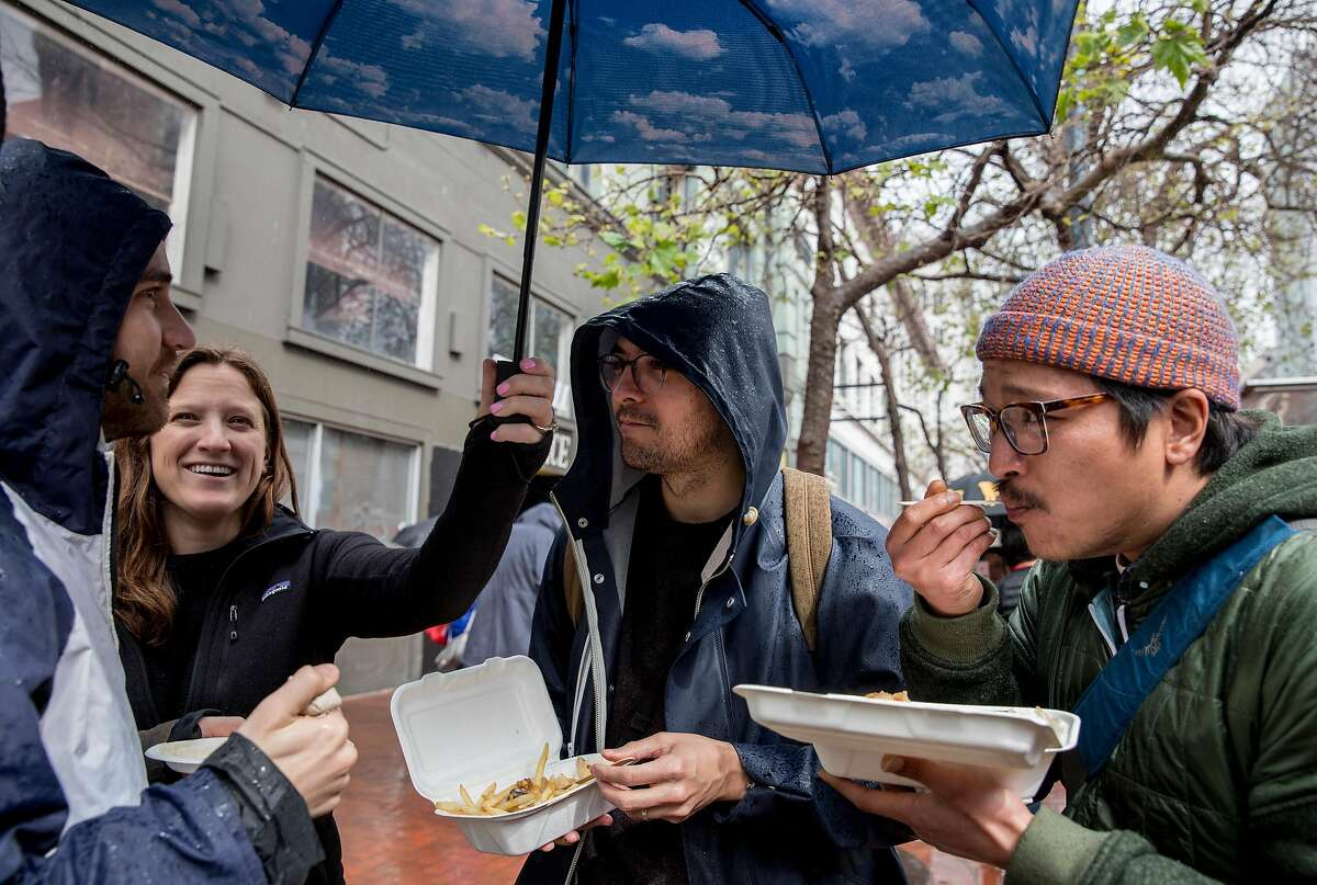 Brian Green (center) and Jeremy Reyes (right) enjoy lunch with friends while hanging out near food trucks along Market Street near 6th Street in San Francisco, Calif. Wednesday, March 6, 2019.
