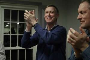 Former Colorado Gov. and Middletown resident John Hickenlooper, left, applauds at a campaign house party Feb. 13 in Manchester, N.H. Hickenlooper declared he's running for the Democratic presidential candidacy Monday.