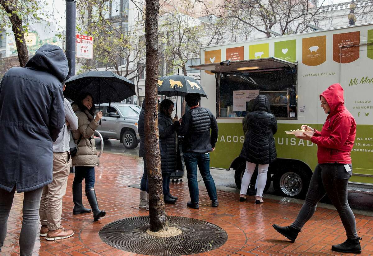 Megan Trotter walks with her food as patrons stand in line at the Mi Morena food truck parked along Market Street near 6th Street in San Francisco, Calif. Wednesday, March 6, 2019.