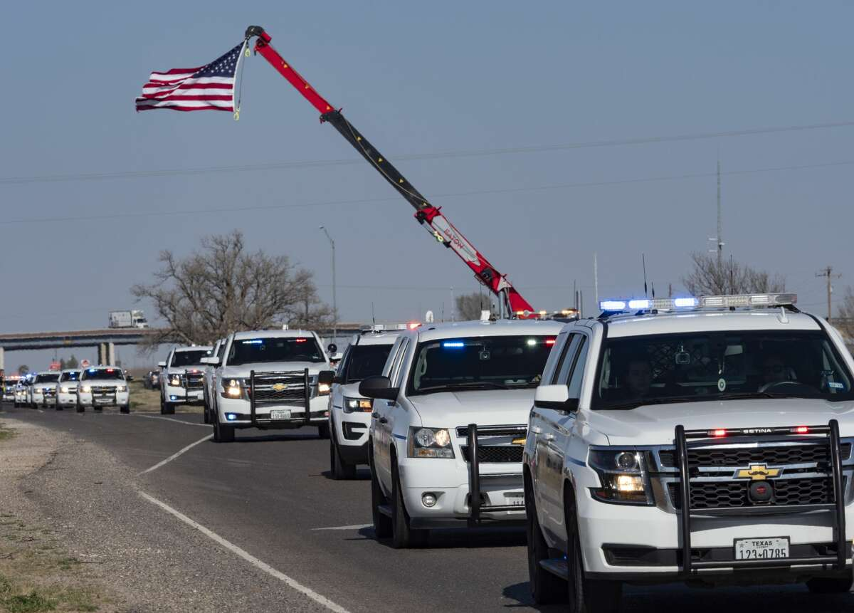Area and state police escort the body of MPD Officer Nathan Heidelberg back to Midland 03/06/2019 as they make their way from I-20 to drive north up Loop 250 under the American Flag hung from an area wrecker boom. Tim Fischer/Reporter-Telegram