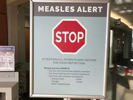 File - In this Jan. 30, 2019, file photo, a sign posted at The Vancouver Clinic in Vancouver, Wash., warns patients and visitors of a measles outbreak. The focus on measles in the Pacific Northwest intensified Friday, March 1, 2019, as public health officials in Oregon announced a new case of the highly contagious disease unrelated to an ongoing outbreak in Washington state that's sickened 68 people so far. (AP Photo/Gillian Flaccus, File)