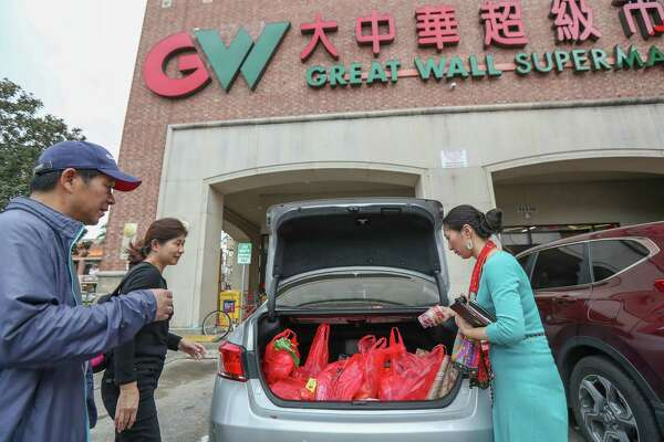 Jack Yang (l-r) and Sally Huang, from Shenzhen, China, shop at the Great Wall Supermarket with the help of Wei Wu, the executive director for the U.S.-China Medical Exchange Monday, Feb. 11, 2019, in Houston.