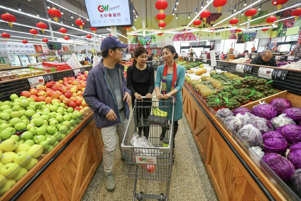 Jack Yang and Sally Huang from Shenzhen, China, shop with help from Wei Wu, right, of the U.S.-China Medical Exchange.
