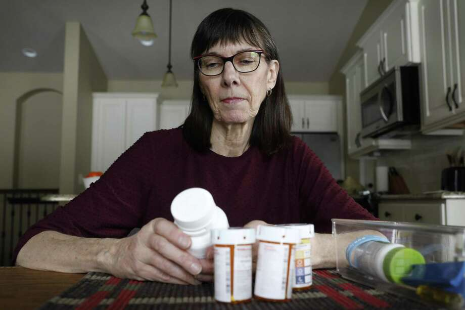 A retired teacher in Iowa examines the expensive prescription drugs she takes. A reader says such costs also are rising for retired teachers in Texas, who deserve cost-of-living increases. Photo: Charlie Neibergall /Associated Press / Copyright 2019 The Associated Press. All rights reserved