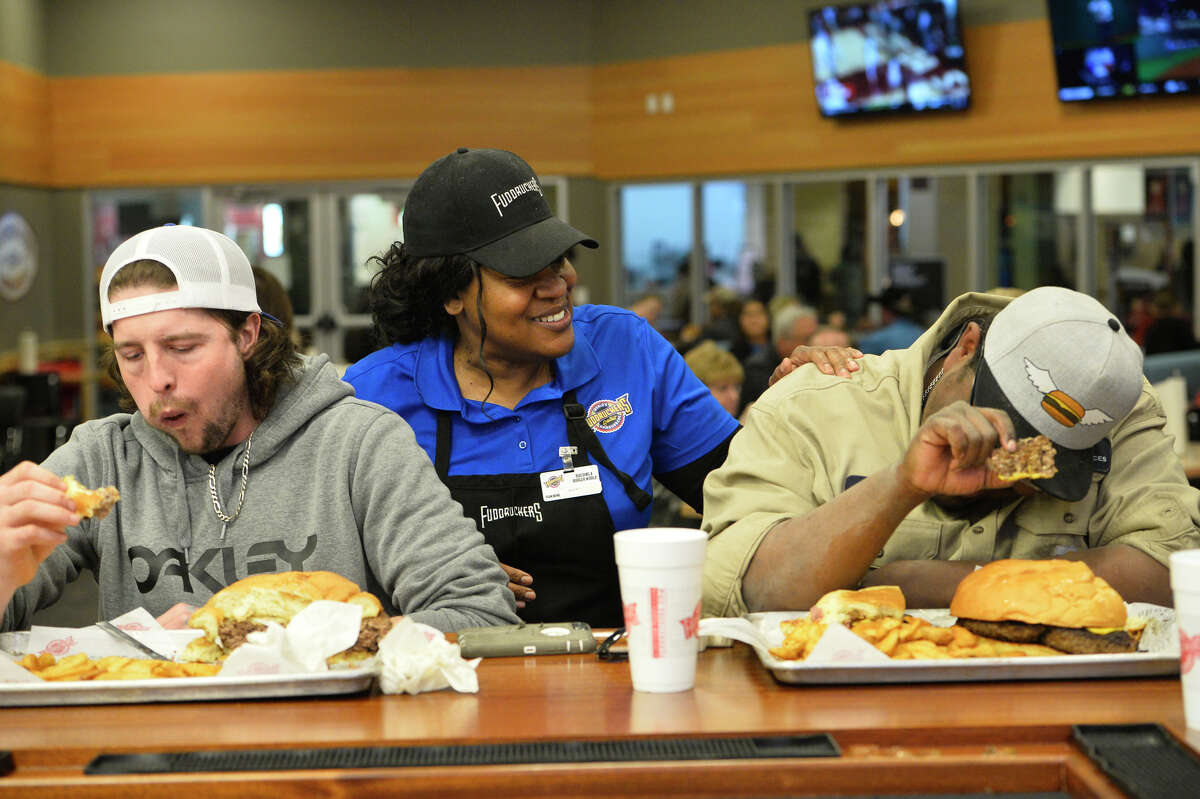 Deborah Keys, Fuddruckers manager, checks on Zach Biggs, left, and Jordon Ramsoure, right, as they participate in a three-pound burger challenge March 6, 2019, at Fuddruckers in Midland Park Mall. Contestants attempted to eat the burger, oversize bun, and a pound of fries in one hour. James Durbin / Reporter-Telegram