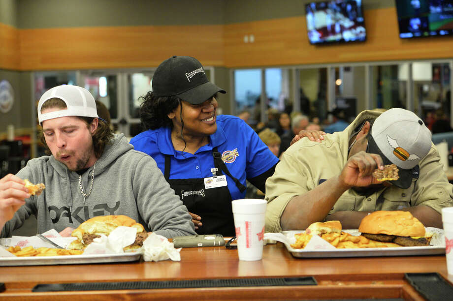 Deborah Keys, Fuddruckers manager, checks on Zach Biggs, left, and Jordon Ramsoure, right, as they participate in a three-pound burger challenge March 6, 2019, at Fuddruckers in Midland Park Mall. Contestants attempted to eat the burger, oversize bun, and a pound of fries in one hour.  James Durbin / Reporter-Telegram Photo: James Durbin / Midland Reporter-Telegram / ? 2019 All Rights Reserved