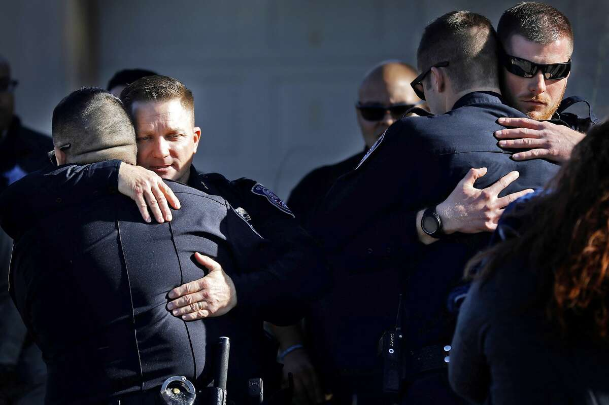 Midland Police Chief Seth Herman (center left) hugs fellow officers after a procession delivered the body of Midland Police Department Officer Nathan Heidelberg to Nalley-Pickle and Welch Funeral Home March 6, 2019. Officer Heidelberg was shot by a homeowner while responding to a burglary alarm at a residence on March 5. James Durbin / Reporter-Telegram