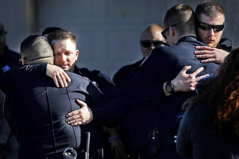 Midland Police Chief Seth Herman (center left) hugs fellow officers  after a procession delivered the body of Midland Police Department Officer Nathan Heidelberg to Nalley-Pickle and Welch Funeral Home March 6, 2019. Officer Heidelberg was shot by a homeowner while responding to a burglary alarm at a residence on March 5. James Durbin / Reporter-Telegram Photo: James Durbin / Midland Reporter-