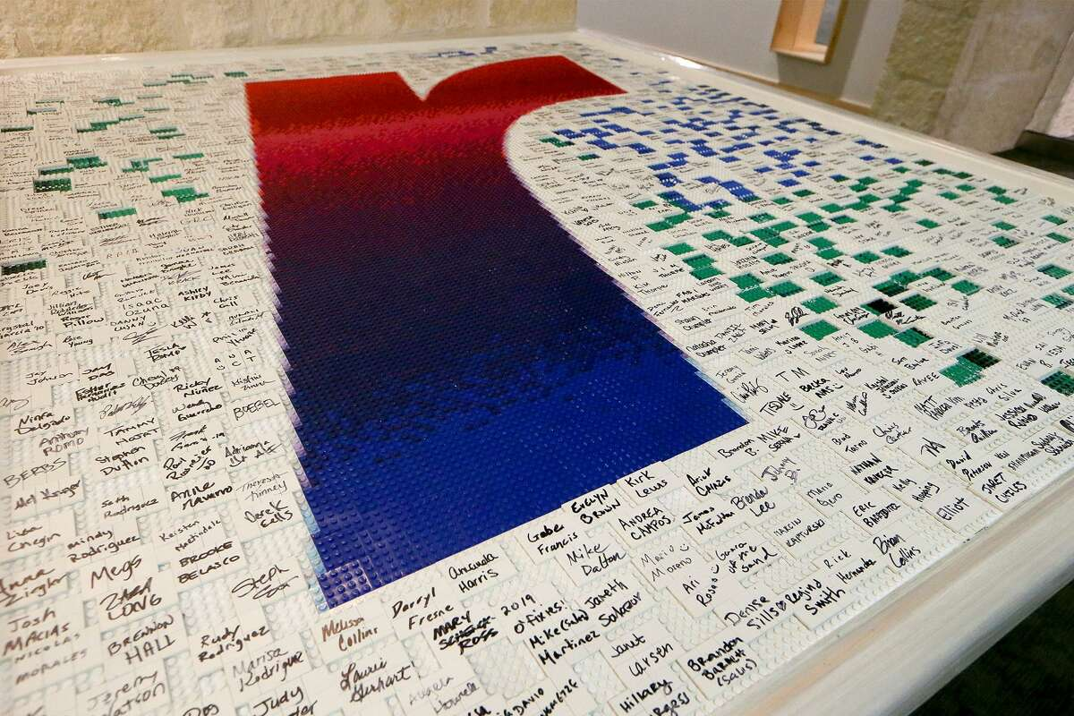 """Rackspace's new logo, a gradient """"r"""" made from Legos and signed by Rackers, on display in the company's lobby on Wednesday, March 6, 2019."""
