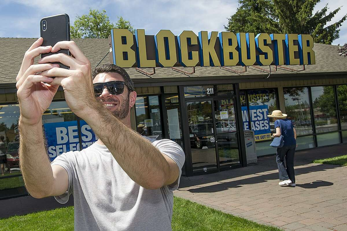 File - In this July 13, 2018 file photo, Scott Thornton takes a selfie in front of the Bend, Ore., Blockbuster. The Blockbuster store in Bend, Oregon became the last one in the US last year. And now it's the only one in the world.