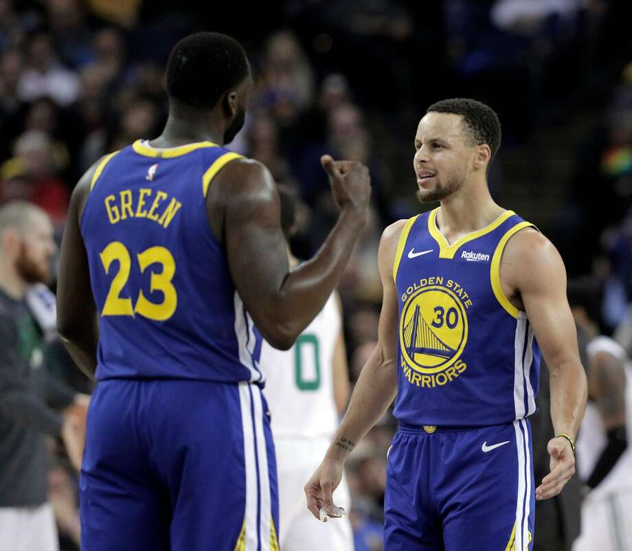 Stephen Curry (30) talks to Draymond Green (23) after Green was called for a questionable foul and argued with the official in the first half as the Golden State Warriors played the Boston Celtics at Oracle Arena in Oakland, Calif., on Tuesday, March 5, 2019. Photo: Carlos Avila Gonzalez, The Chronicle