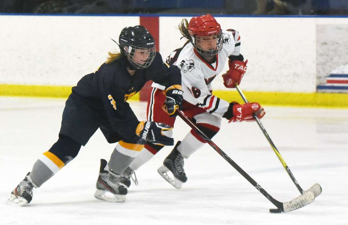 Simsbury's Mackenzie Chapman (3) and New Canaan's Tess Hobbs (18) race for the puck during the CHSGHA State semifinals at The Rinks at Shelton on Wednesday.
