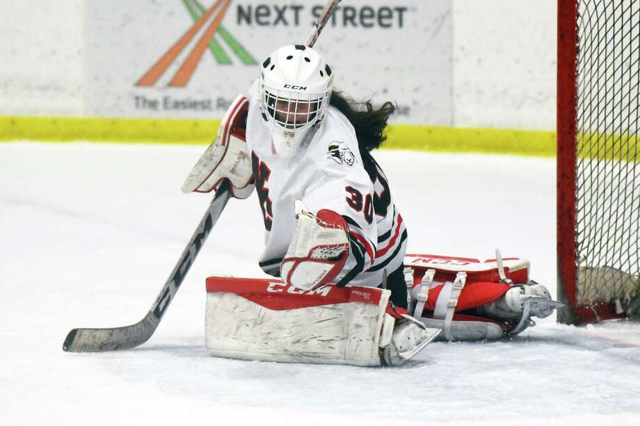 New Canaan goalie Blythe Novick makes a glove save during the CHSGHA State semifinals at The Rinks at Shelton on March 6. Photo: David Stewart / Hearst Connecticut Media / Connecticut Post