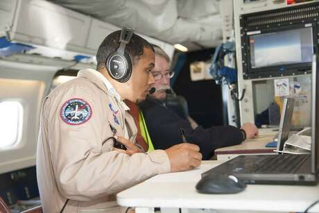 Mission managers Matt Berry, left, and Chris Jennison work aboard NASA's DC-8 Flying Laboratory during its Polar Winds mission in Iceland in 2015.