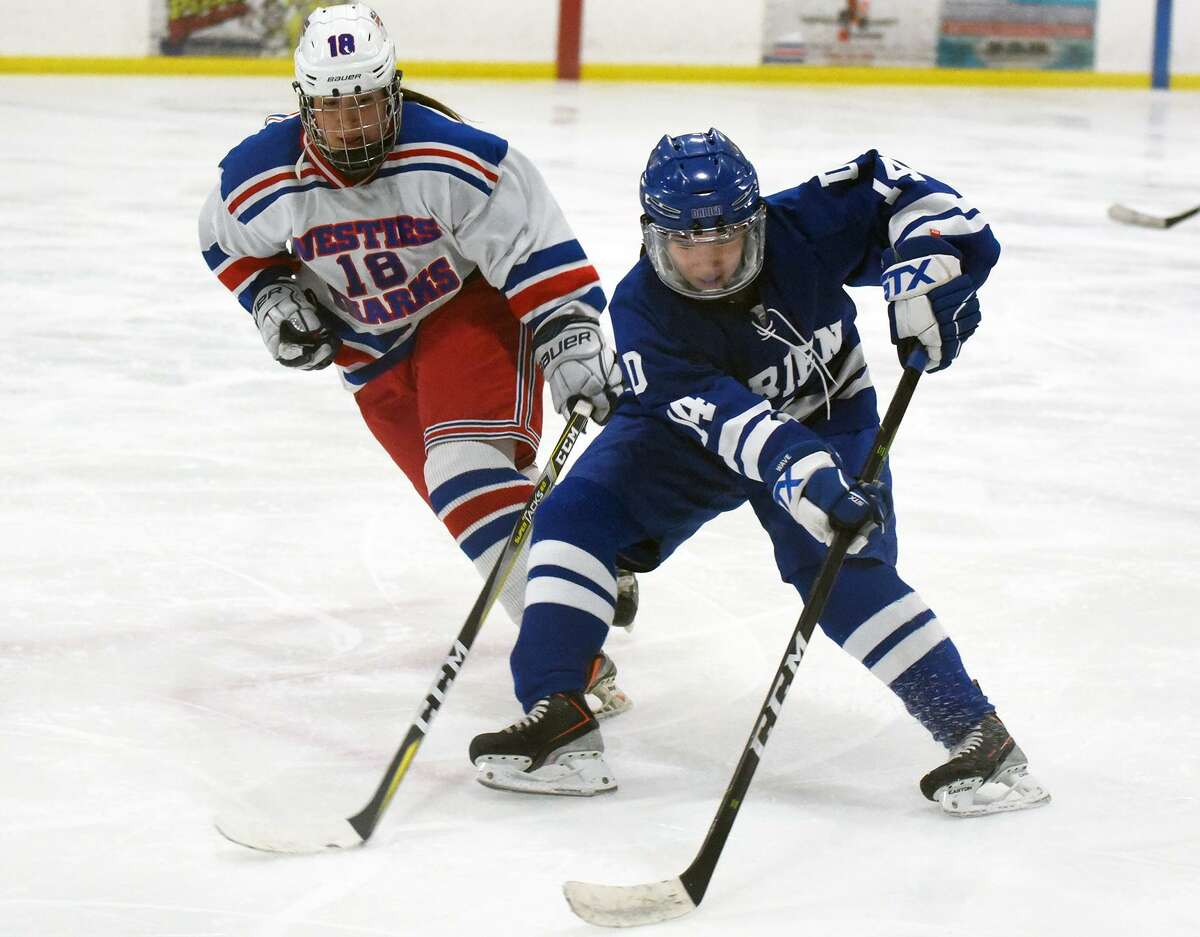 Darien's Caitlin Chan (14) controls the puck in front of West Haven's Brooke McNabola (18) during the CHSGHA state semifinals at The Rinks at Shelton on Wednesday, March 6.