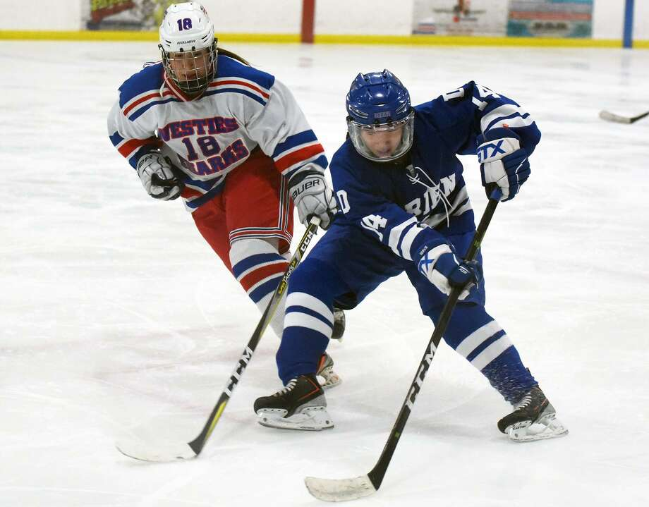 Darien's Caitlin Chan (14) controls the puck in front of West Haven's Brooke McNabola (18) during the CHSGHA state semifinals at The Rinks at Shelton on Wednesday, March 6. Photo: David Stewart / Hearst Connecticut Media / Connecticut Post