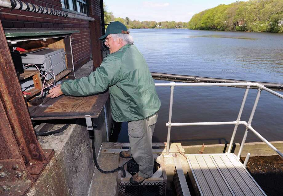A volunteer checks his electronic fish counter at the fishway adjacent to the Mianus River dam on April 27, 2012. More than 50,000 alewives were counted going through the fishway in a 24-hour period. Photo: File / Hearst Media Connecticut / Greenwich Time