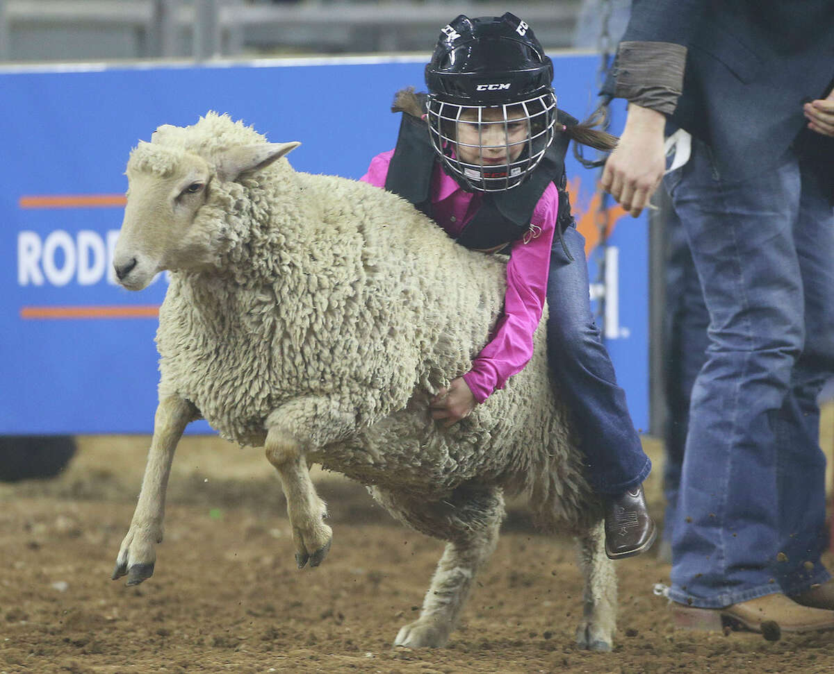 Greer Thorne, 6, of Houston holds onto her sheep during the Mutton Bustin at RodeoHouston at NRG Stadium on Wednesday, March 6, 2019.