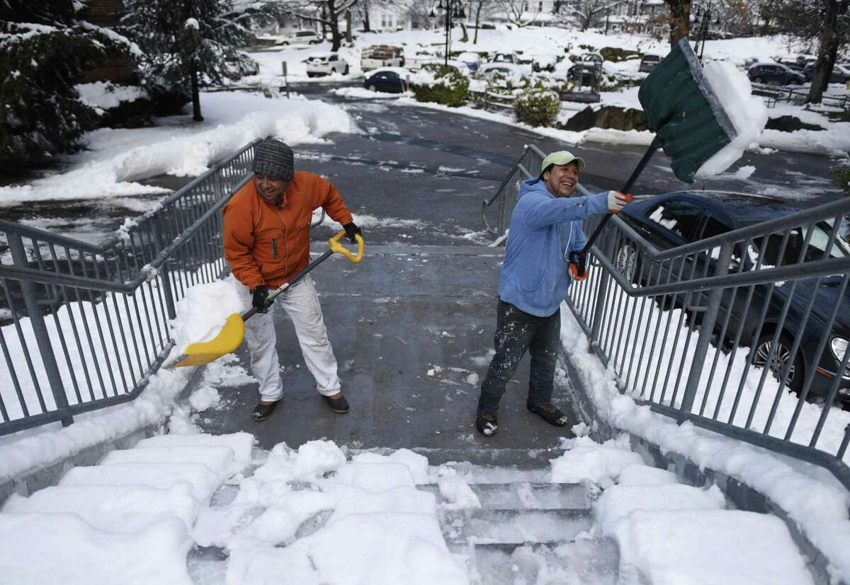 It wasn't the storm of the century, but Manlio Franco, left, and Mario Arana went to work shoveling 8 inches of snow from steps at the Wilbur Peck public housing complex in Greenwich, Conn. Monday, March 4, 2019. The heavy, wet snow caused school cancellations, power outages, traffic accidents and delayed the opening of Town Hall.