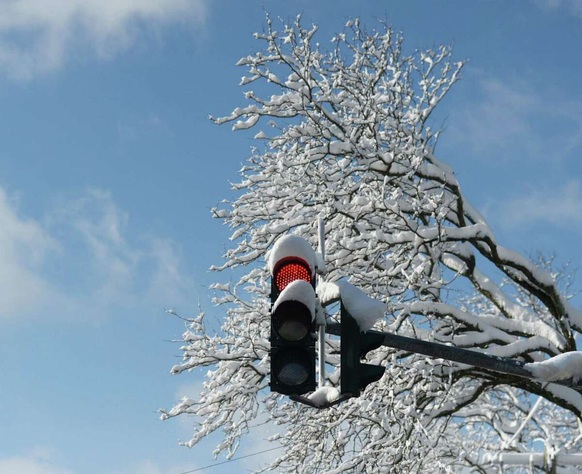 Snow covers a traffic light and tree branches in Greenwich, Conn. Monday, March 4, 2019. Greenwich received 8 inches of heavy, wet snow that caused school cancellations, power outages, traffic accidents and delayed the opening of Town Hall.