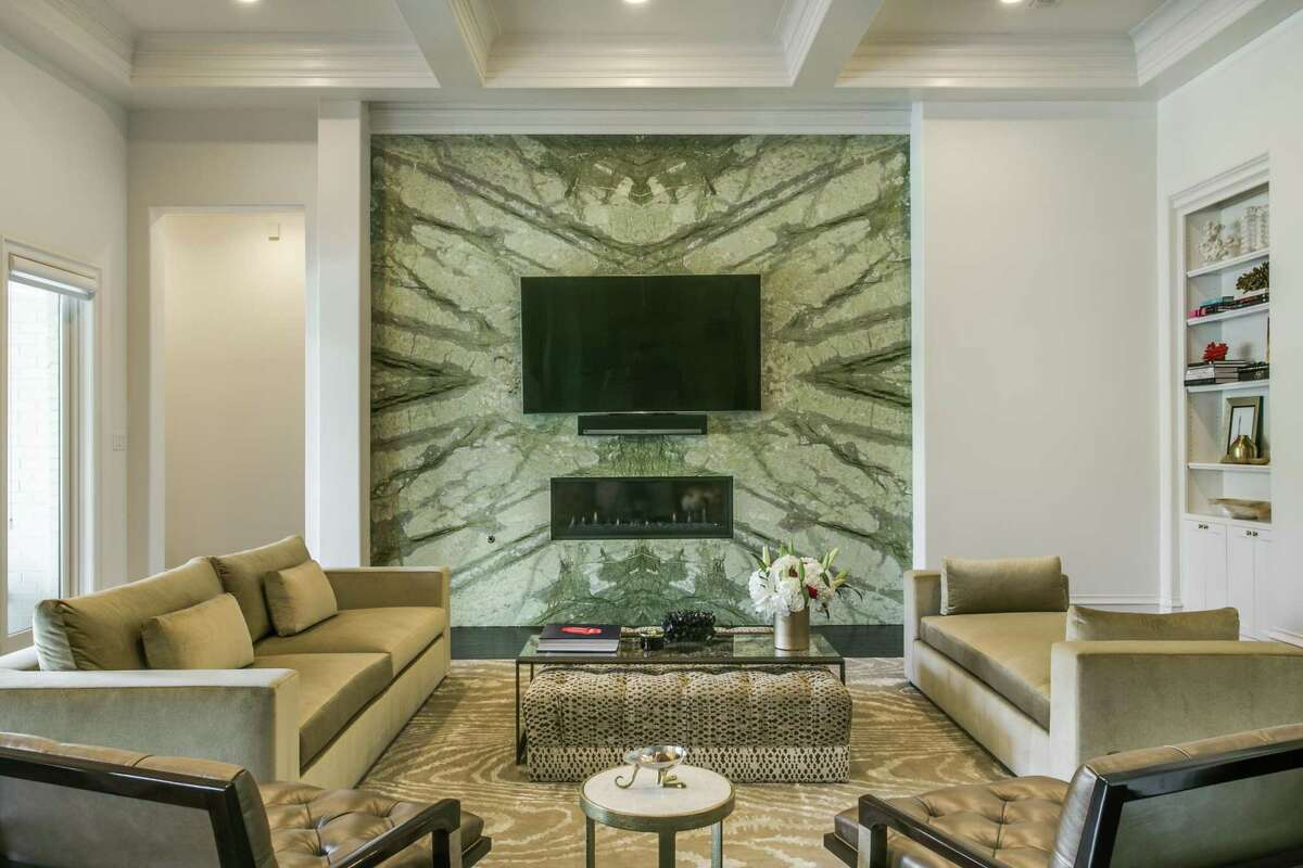 Book-matched slabs of Verde Aurora marble from Aria Stone Gallery were used around this fireplace.