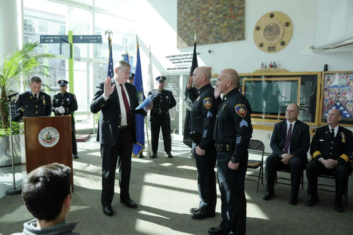 Mayor David Martin swearing in James Comstock and Peter Malanga as sergeants in the lobby of Government Center on Wednesday. Sitting on the right looking on is Director of Public Safety Ted Jankowski and police Chief Jon Fontneau.