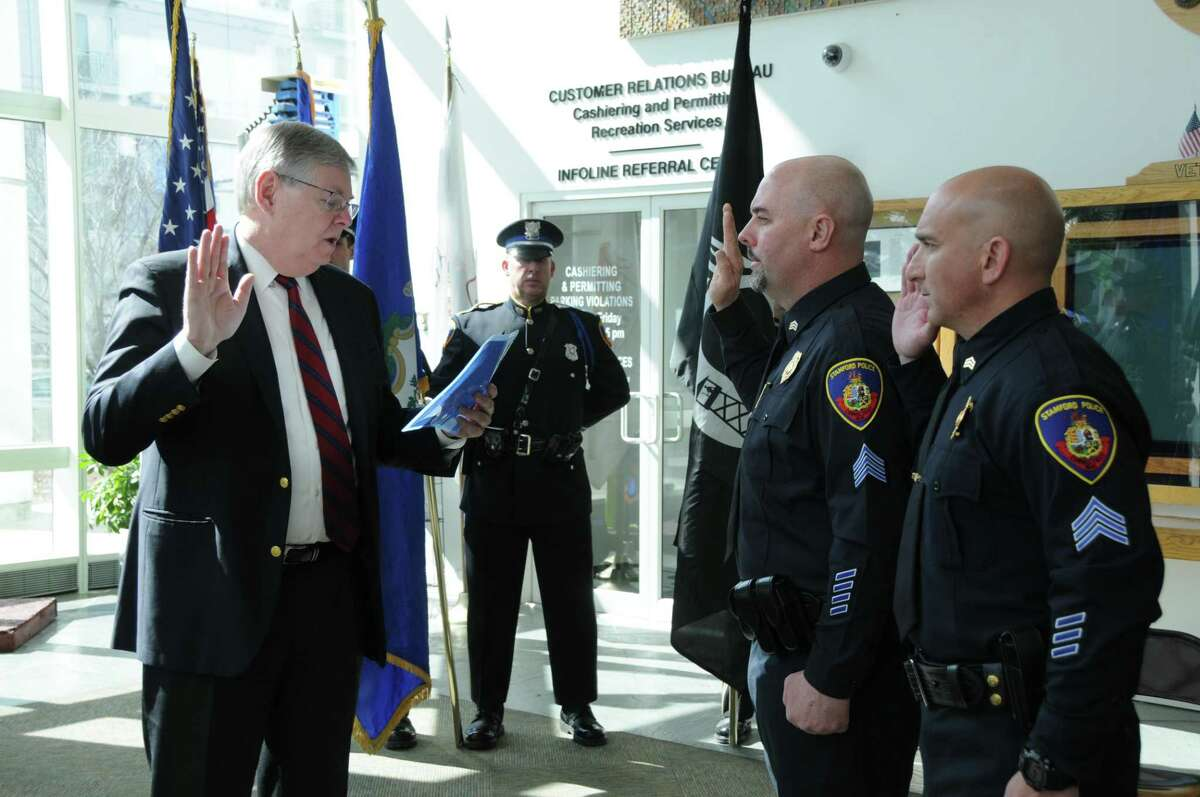 Mayor David Martin swearing in James Comstock and Peter Malanga as sergeants in Government Center on Wednesday.