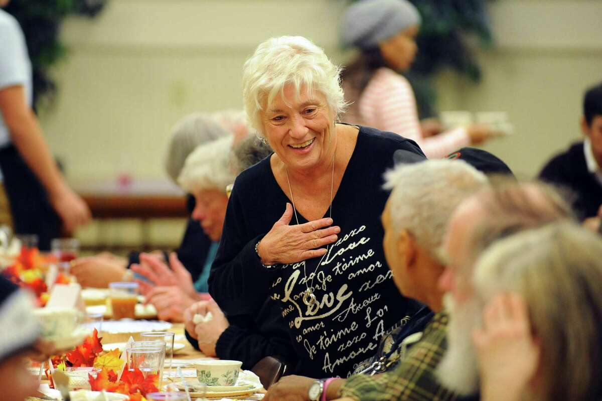 Marion McGarry, a member of the board of representatives for Stamford's 12th district, smiles as she chats with guests at the First Congregational Church's Thanksgiving Day dinner in Stamford, Conn. on Thursday, Nov. 24, 2016.