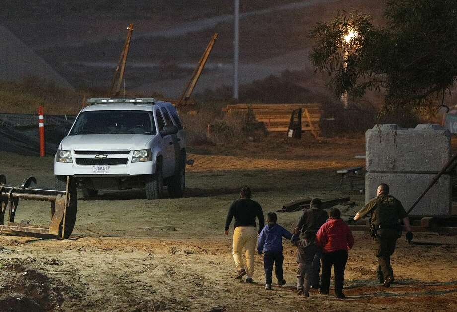 FILE - In this Dec. 3, 2018, file photo, migrants are escorted by a U.S. Border Patrol agent as they are detained after climbing over the border wall from Playas de Tijuana, Mexico, to San Ysidro, Calif. The Trump administration's effort to make asylum seekers wait in Mexico explicitly targets Spanish-speakers and people from Latin America, according to internal guidelines of a highly touted strategy to address the burgeoning number of Central Americans arriving at U.S. borders. (AP Photo/Rebecca Blackwell, File) Photo: Rebecca Blackwell, Associated Press