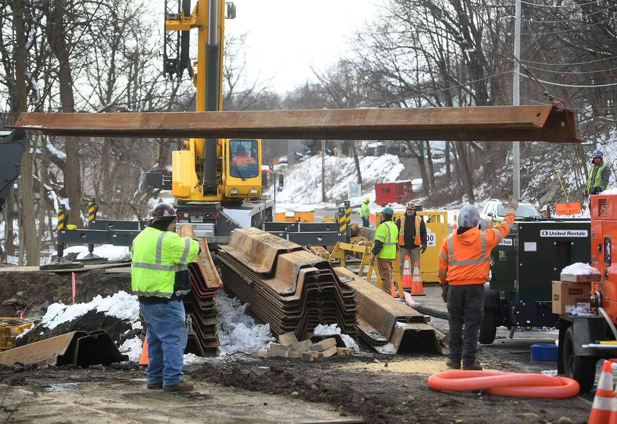 Steel shoring is unloaded at the site of the sewer pipe break on Pershing Drive in Ansonia, Conn. on Wednesday, March 6, 2019.