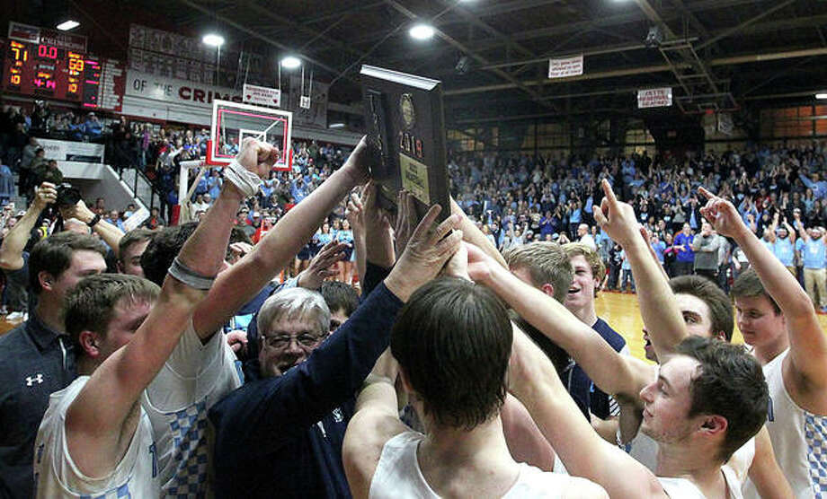 Members of the Triopia basketball team celebrate with their plaque after winning the Jacksonville Super-Sectional game over Okawville earlier this week. Triopia will play in the Class 1A state semifinals Friday in Peoria. Photo: Dennis Mathes, JJC | For The Telegraph