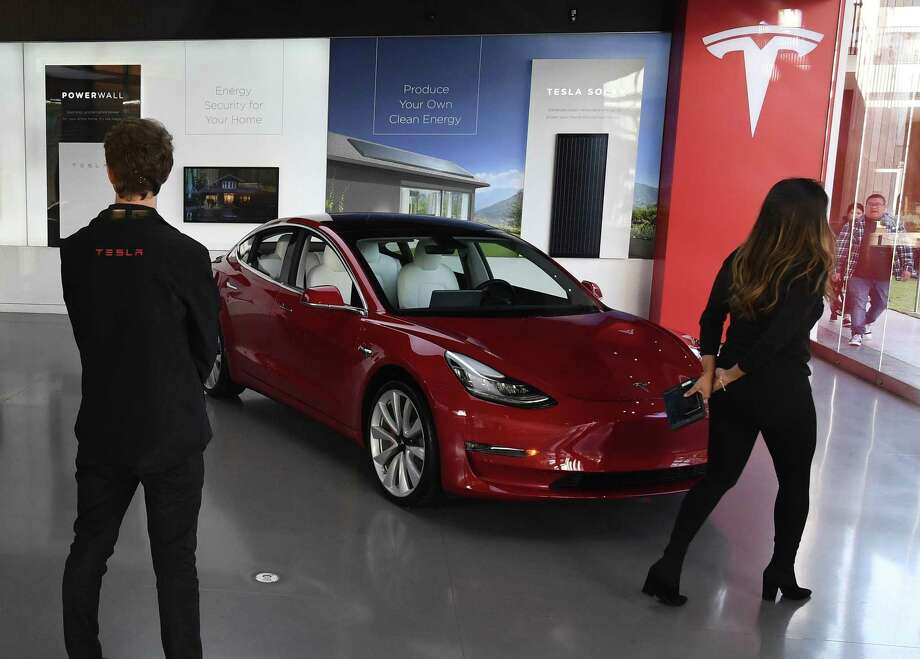 Tesla cars are seen for sale at a shopping mall showroom March 4 in Los Angles after the company indicated it would be closing showrooms and in the future selling its cars online. Tesla unveiled its lowest-priced Model 3, an electric car designed for the masses, at a base price of $35,000, with deliveries promised within one month. Photo: MARK RALSTON / AFP /Getty Images / AFP or licensors