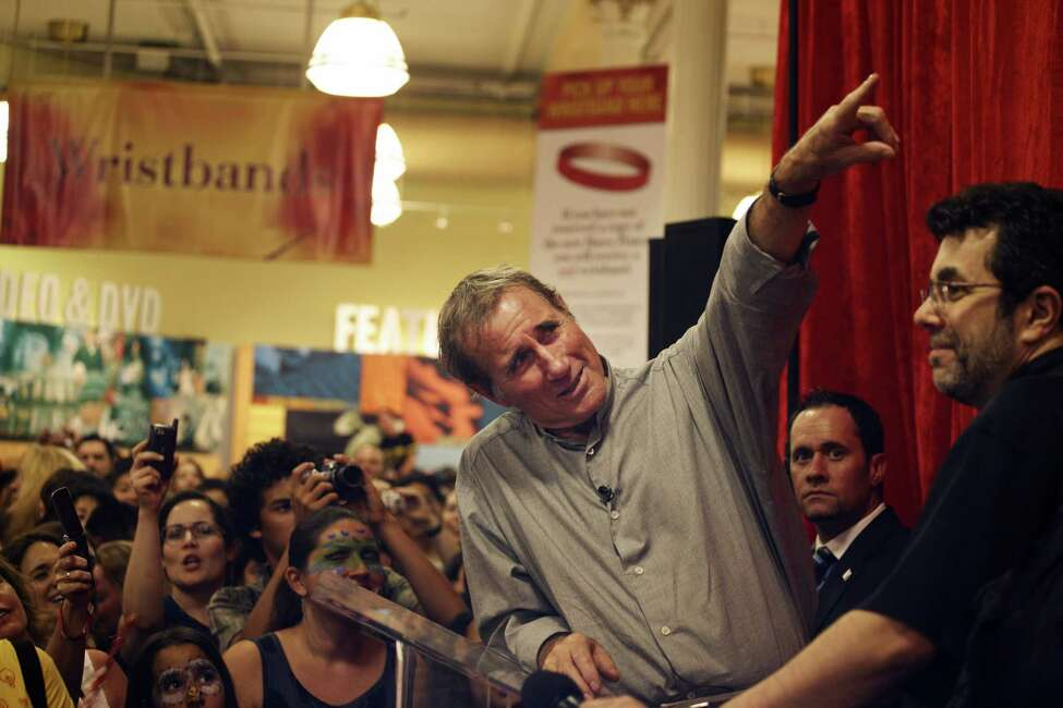 Actor Jim Dale, who provided the voices for the audio books, points to a clock in the Barnes & Noble Booksellers Union Square before author J.K. Rowling's novel