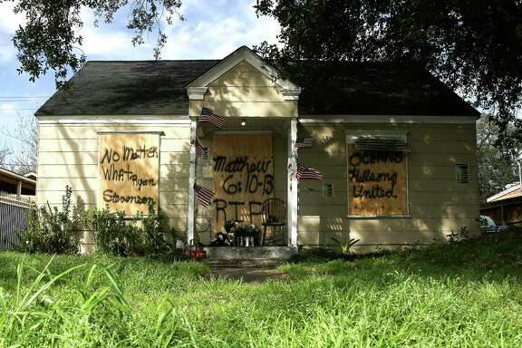 Boards cover the front of a home at 7815 Harding Street in Houston, Friday, Feb. 15, 2019, where the occupants of the home were shot to death during a police raid on Jan. 28. A lead investigator lied in an affidavit justifying a drug raid at the Houston home in which two residents were killed and four undercover officers were shot and wounded during a gun battle, the city's police chief said Friday. (Elizabeth Conley/Houston Chronicle via AP)