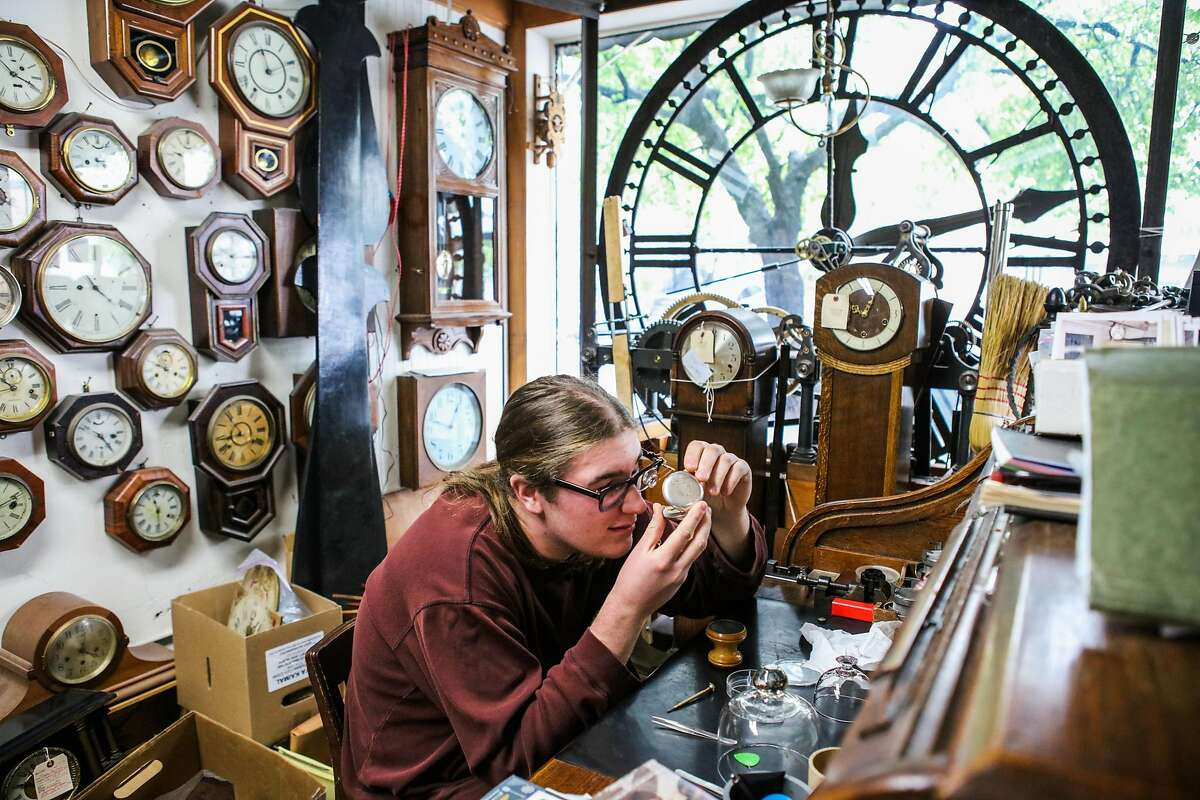 Clock-maker's apprentice Maxwell Nesbet, looks closely at a pocket watch as he repairs it, at his desk at Dorian Clair's clock repair shop in Noe Valley, San Francisco, California, on Friday, March 11, 2016. Maxwell may be helping Dorian Clair reset the time on the Ferry Building clock on Sunday for daylight savings.