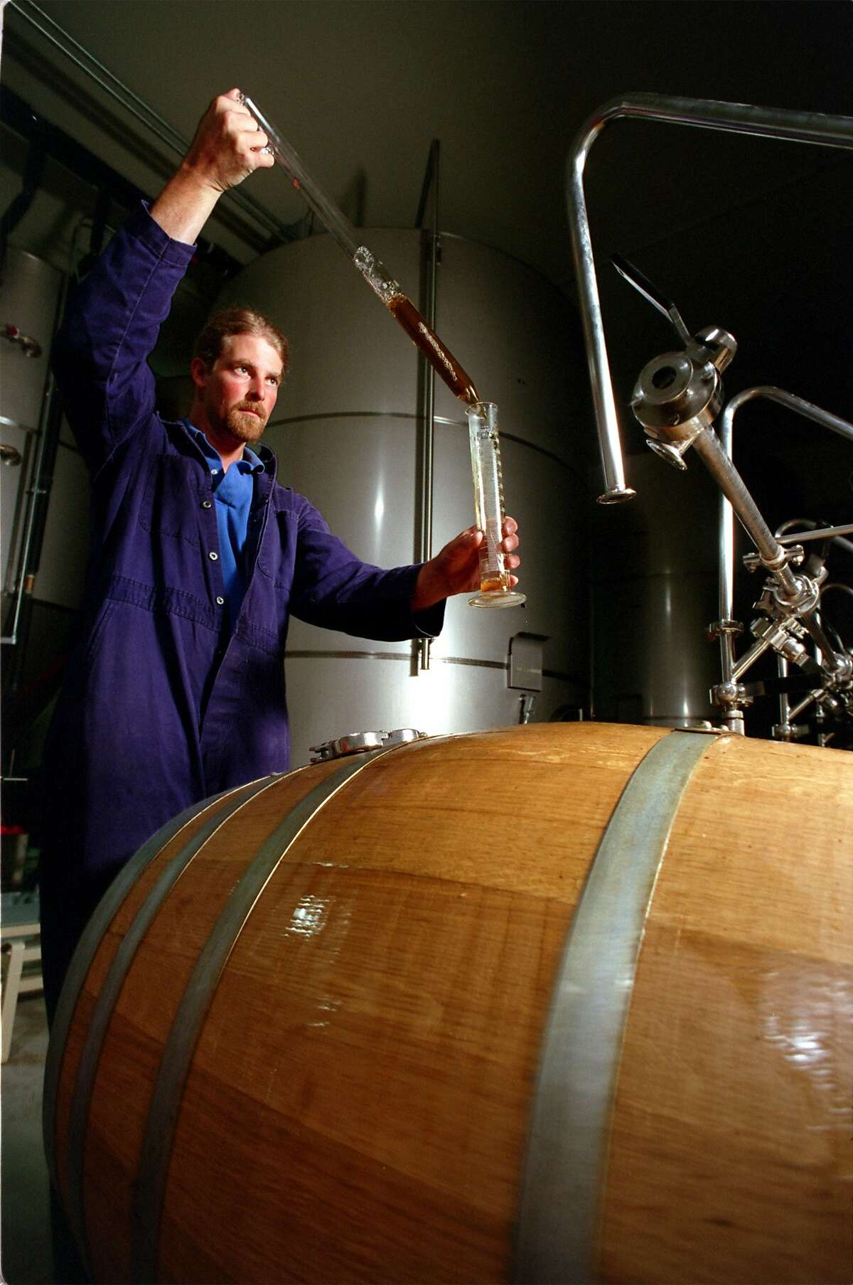 Firestone Walker Brewmaster, Jeffers Richardson, samples beer fermenting in the 'union' a system of American Oak barrels that the beer rests in during part of the brewing process.