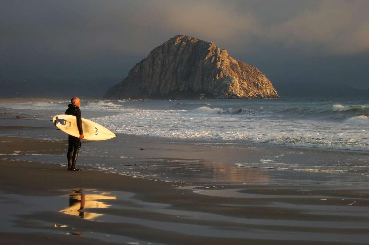 A surfer looks out at the Pacific Ocean as Morro Rock stands under evening sun on July 8, 2014 in Morro Bay, California. The route of Highway 1 between San Francisco and Los Angeles, which passes through Big Sur, is a popular tourist destination.