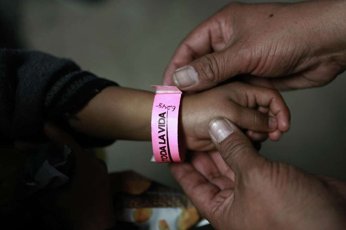 A child in Ciudad Juarez wears a bracelet that indicates his place in line to submit his request for U.S. asylum. The crisis at the border is a humanitarian one.
