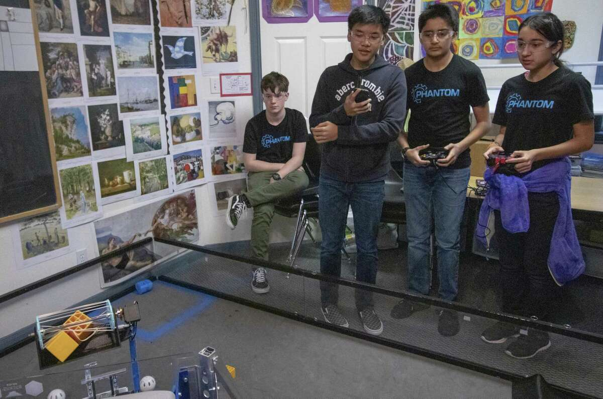 Shreyas Vatts, 13, (center right) and Diya Shah, 13, (far right) take command of team Phantom robot Erik with contorllers during a practice session Wednesday, March 6, 2019 at Rubicon Academy in Conroe.