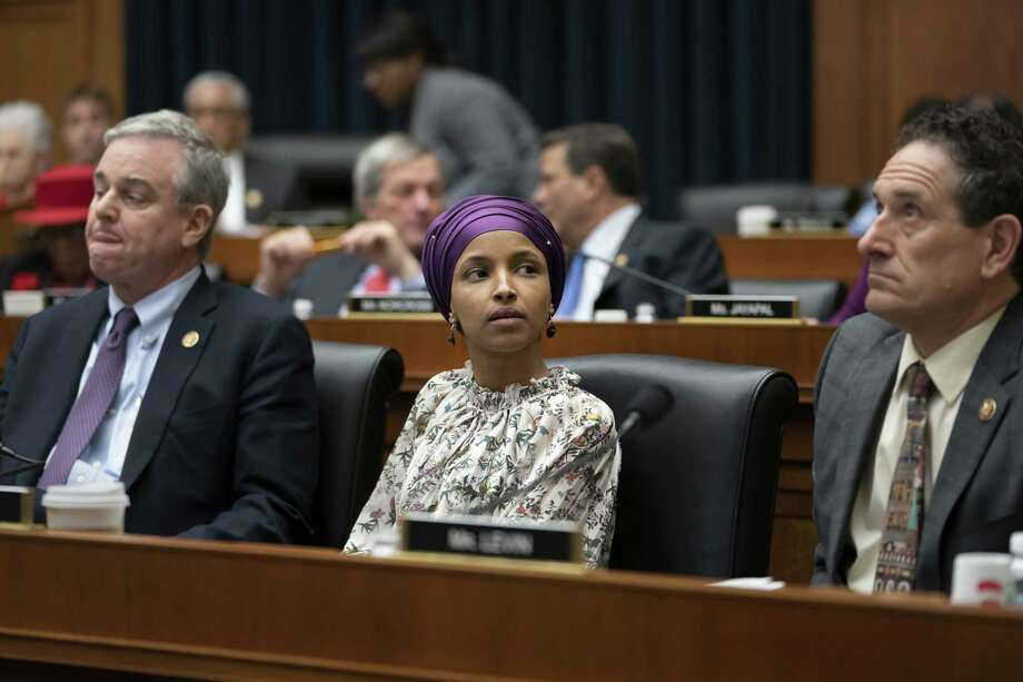 """Rep. Ilhan Omar, D-Minn., sits with fellow Democrats, Rep. David Trone, D-Md., left, and Rep. Andy Levin, D-Mich., right, on the House Education and Labor Committee during a bill markup, on Capitol Hill in Washington, Wednesday, March 6, 2019. Omar stirred controversy last week saying that Israel's supporters are pushing U.S. lawmakers to take a pledge of """"allegiance to a foreign country."""" Omar is not apologizing for that remark, and progressives are supporting her. (AP Photo/J. Scott Applewhite) Photo: J. Scott Applewhite / Associated Press / Copyright 2019 The Associated Press. All rights reserved."""