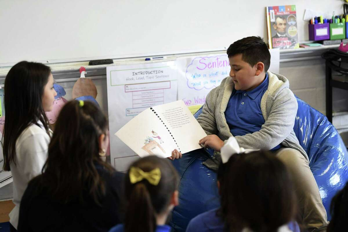 Jose Guajardo reads from a book that he wrote during the weekly Literacy Clinic given by Our Lady of the Lake University education students at Rodriguez Elementary on Thursday, March 7, 2019.