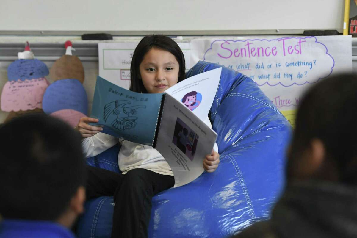 Angela Garza reads from a book that she wrote during the weekly Literacy Clinic given by Our Lady of the Lake University education students at Rodriguez Elementary on Thursday, March 7, 2019.