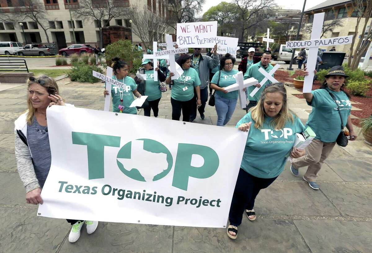 Members of the Texas Organizing Project march around the Bexar County courthouse Thursday before holding a news conference to present a petition demanding an end to the practice of cash bail in the county.