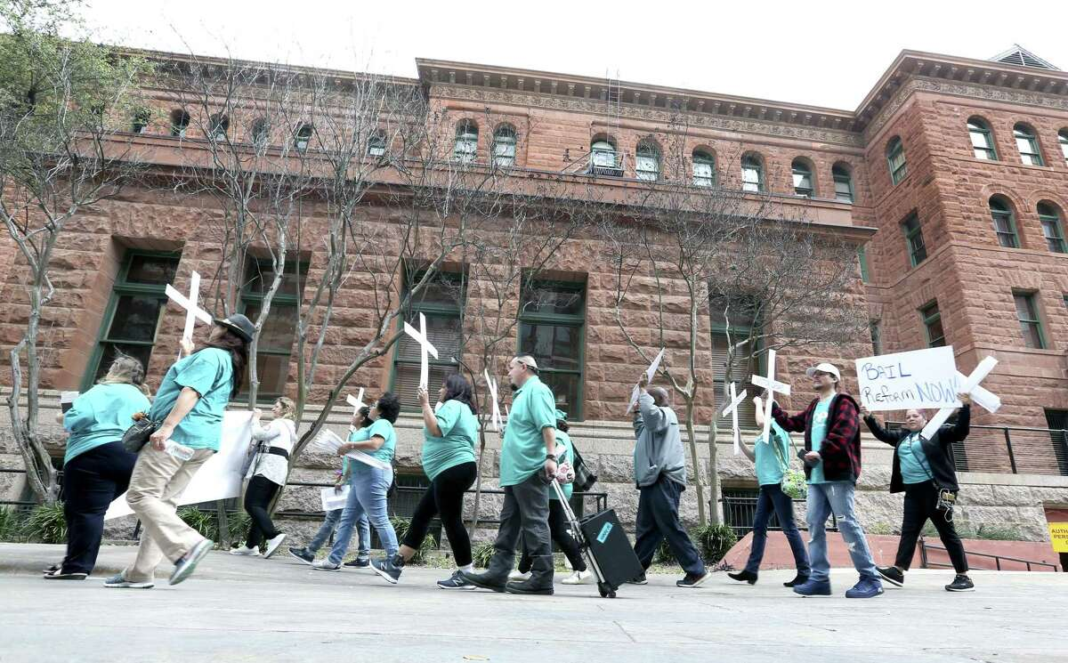 Members of the Texas Organizing Project march around the Bexar County courthouse Thursday, March 7, 2019 before holding a press conference to ask Bexar County judges to create a concrete plan to end the practice of cash bail in the county. The group was also planning on presenting petition signatures gathered online in conjunction with civil rights advocacy group Color of Change to the judges.